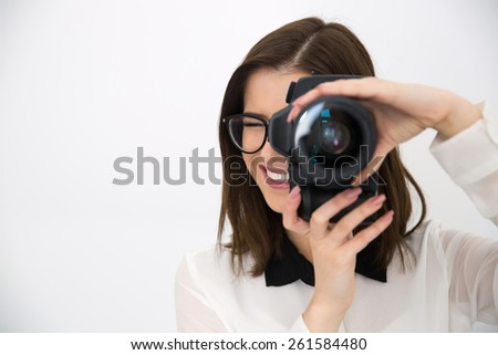 Smiling female photographer with camera over gray background - stock photo