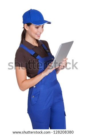 Smiling Female Plumber Working On Digital Tablet. Isolated On White - stock photo