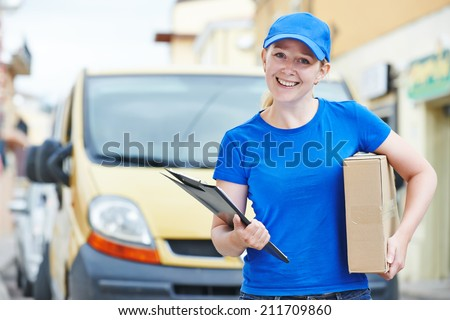 Smiling female postal delivery courier woman outdoors  in front of cargo van delivering package - stock photo