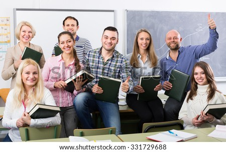 Smiling female professor and cheerful students posing in classroom at extension courses  - stock photo