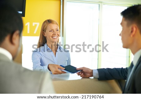 Smiling female returning passport and tickets to businessman in airport - stock photo