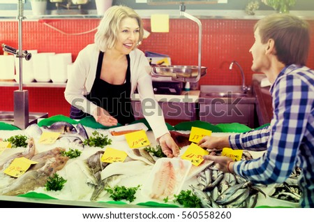 Smiling female seller and ordinary male customer choosing fresh fish at market