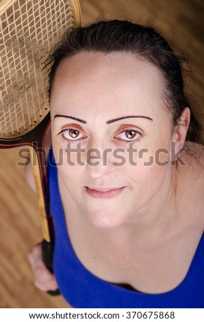 Smiling female squash player holding racket in sports gym. - stock photo