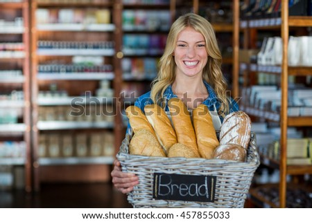 Smiling female staff holding a basket of breads in supermarket