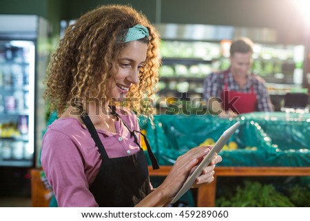 Smiling female staff using digital tablet in organic section of supermarket - stock photo