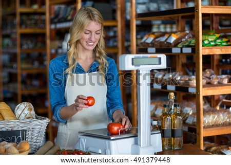 Smiling female staff weighting vegetables on scale in supermarket