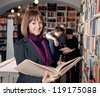 Smiling female student holding book. Students in the background. - stock photo