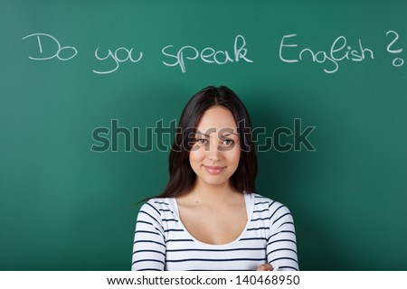 smiling female student in classroom learning english - stock photo