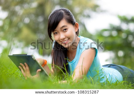 Smiling female student lying on grass with digital tablet and looking at camera