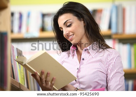 smiling female student reading a book in a bookstore - stock photo