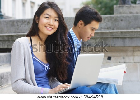 Smiling female student sitting on a stairs at university with a male friend at the background - stock photo