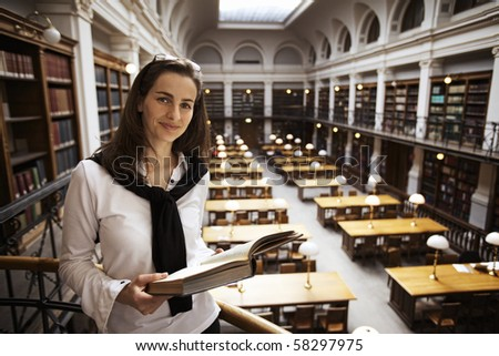 Smiling female student standing at handrail upstairs in old university library reading a book. - stock photo