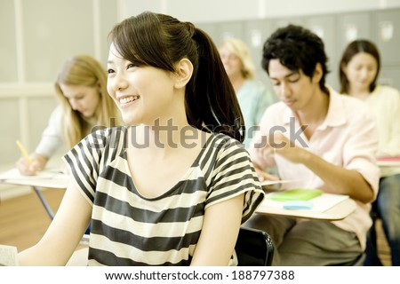 smiling female student studying in classroom - stock photo