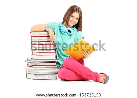 Smiling female student with headphones posing near many books isolated on white background