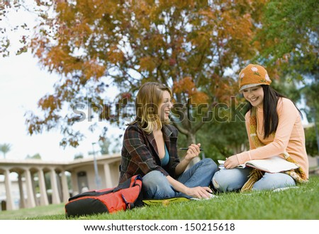 Smiling female students studying on college campus - stock photo