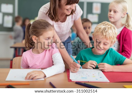 Smiling female teacher helping a young boy at primary school with his notes watched by two young girls - stock photo