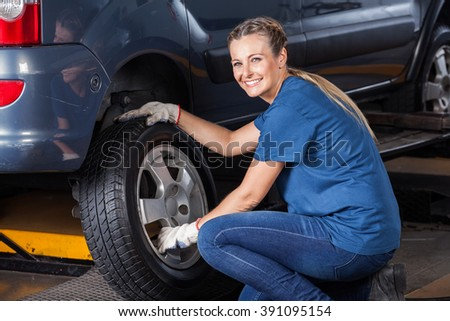 Smiling Female Technician Adjusting Car Tire - stock photo