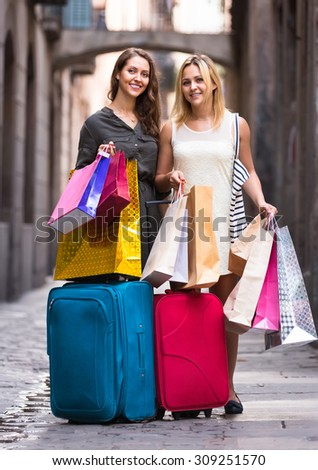Smiling female tourists with suitcases and shopping bags in the street