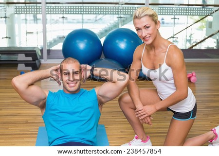 Smiling female trainer assisting young man with abdominal crunches at fitness studio - stock photo