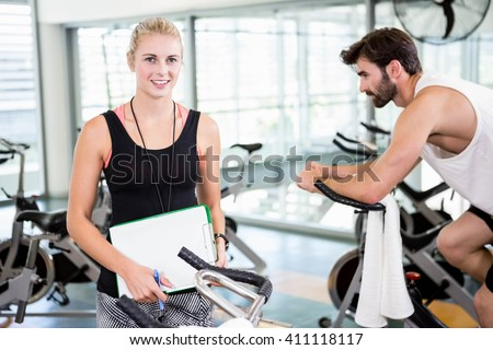 Smiling female trainer looking at the camera and man using exercise bike