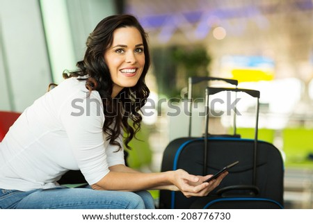 smiling female traveller using tablet computer while waiting for her flight at airport - stock photo