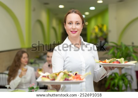 Smiling female waiter serving guests table in restaurant - stock photo