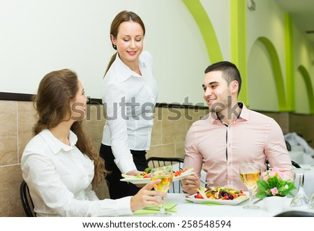 Smiling female waiter with plates serving visitors table in cafe