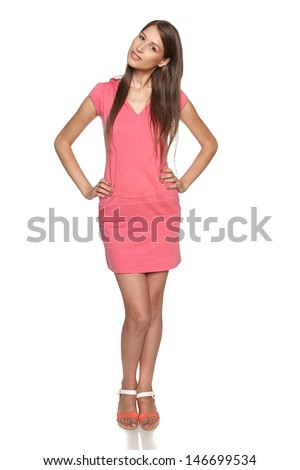 Smiling female wearing sport style pink dress posing with hands on hips,  isolated on white background - stock photo