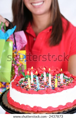 smiling female with birthday cake and presents