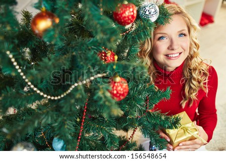 Smiling female with giftbox looking at camera out of decorated firtree - stock photo
