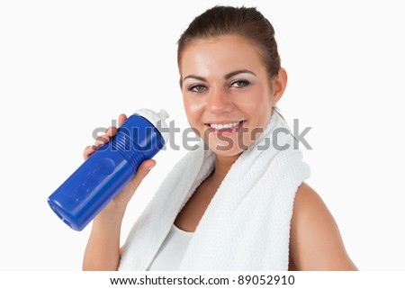Smiling female with her bottle after workout against a white background