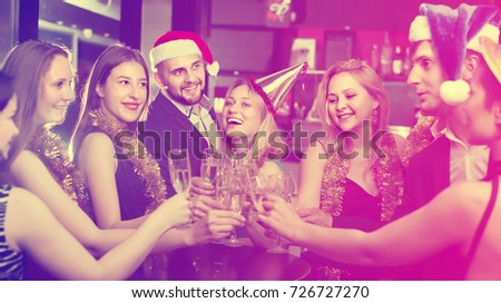 Smiling females and males celebrating new year in the club at night