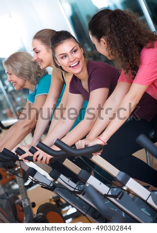 smiling females riding stationary bicycles in modern gym for women