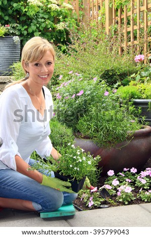 Smiling fifty year old lady gardener outside in the garden holding a pack of lobelia.
