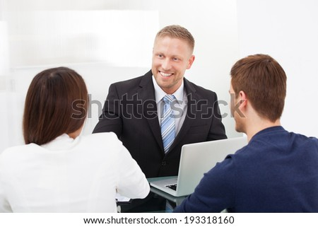 Smiling financial advisor discussing with young couple at office desk - stock photo