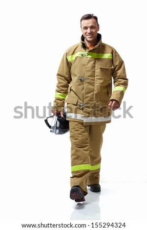 Smiling firefighter in uniform on a white background - stock photo