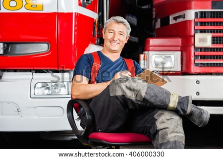 Smiling Firefighter Sitting On Chair Against Trucks - stock photo