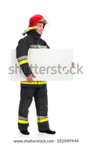Smiling fireman in red helmet standing and holding placard under his arm. Full length studio shot isolated on white.