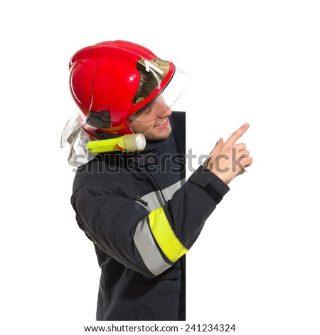 Smiling fireman in red helmet standing behind placard pointing and reading. Waist up studio shot isolated on white. - stock photo