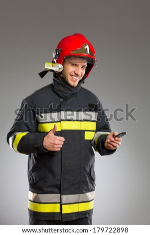 Smiling fireman with smart phone showing thumb up and looking at camera. Waist up studio shot on gray background.