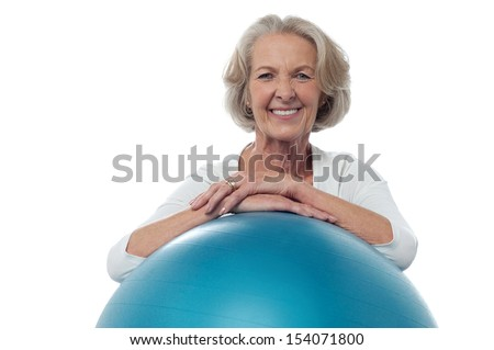 Smiling fit aged lady with exercise ball - stock photo