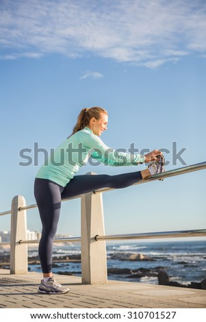 Smiling fit blonde stretching leg on railing at promenade