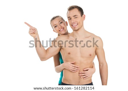 Smiling fit couple looking at camera. Girl hugging man from back while man pointing with his finger - stock photo