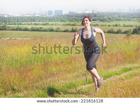Smiling fitness plus size woman running outdoor - stock photo