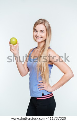 Smiling fitness woman holding apple isolated on a white background - stock photo