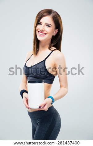 Smiling fitness woman holding jar of protein over gray background. Looking at camera - stock photo