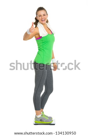 Smiling fitness young woman standing on scales and showing thumbs up - stock photo