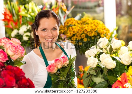 Smiling florist flower shop colorful making bouquet roses market - stock photo