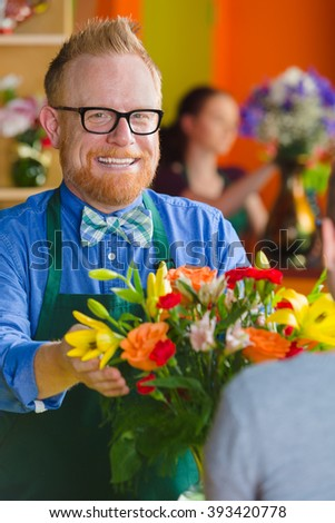 Smiling florist with arrangement in a busy flower shop - stock photo