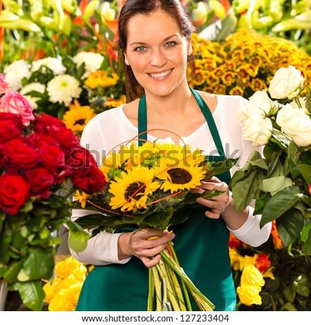 Smiling florist woman bouquet sunflowers flower shop colorful showing - stock photo